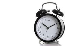 Black alarm clock isolated on white. Backgroundshows ten hours ten minutes of the morning time to get up to wake up and have breakfast morning or evening jog to Royalty Free Stock Image