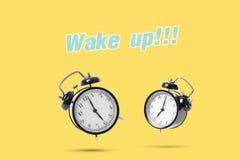 Black alarm clock isolated on yellow background. Concept wake up Royalty Free Stock Photo