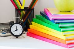 Black alarm clock and multi colored books in stack Royalty Free Stock Image