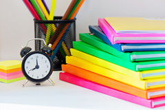 Black alarm clock and multi colored books in stack Royalty Free Stock Photo