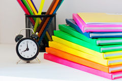 Black alarm clock. Multi colored books in stack Royalty Free Stock Photos