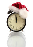 Black alarm clock in a New Year's cap. On a white background Stock Photos