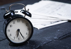 Black alarm clock with newspaper on a wooden table Royalty Free Stock Images