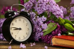 Black alarm clock, an old book and lilac flowers Stock Photography