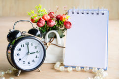 Black alarm clock and open diary with flower Royalty Free Stock Photography