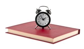 Black alarm clock on red book isolated on white. Background Stock Photos