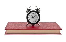 Black alarm clock on red book isolated on white. Background Stock Image
