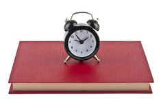 Black alarm clock on red book isolated on white. Background Royalty Free Stock Image