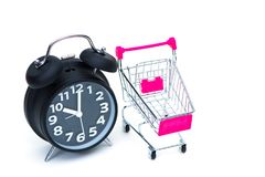 Black alarm clock and shopping cart or supermarket trolley isola. Black vintage alarm clock and shopping cart or supermarket trolley isolated on white background Stock Images