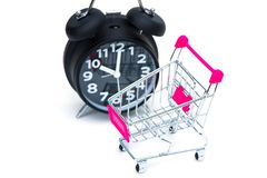 Black alarm clock and shopping cart or supermarket trolley isola. Black vintage alarm clock and shopping cart or supermarket trolley isolated on white background Royalty Free Stock Photo