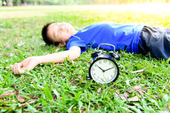 Black alarm clock and sleeping boy in the park Royalty Free Stock Photo
