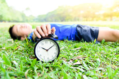 Black alarm clock and sleeping boy in the park Royalty Free Stock Images
