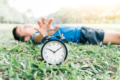 Black alarm clock and sleeping boy in the park Stock Photos