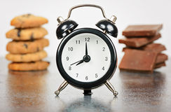 Black alarm clock with sweets Royalty Free Stock Photography