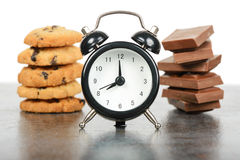 Black alarm clock and sweets Royalty Free Stock Photos
