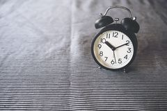 A black alarm clock on the table with blur background stock image