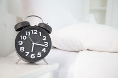 Black alarm clock and white bed Stock Images