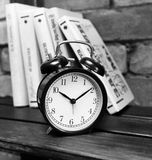 Black alarm clock on a wooden shelf in the background of the books and brick wall Stock Image