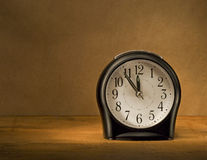 Black alarm clock on a wooden table. Royalty Free Stock Photos