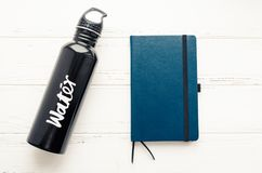 Black aluminum reusable water bottle and notebook. Black aluminum reusable water bottle and dark blue notebook on white shabby chic wooden background. Fitness royalty free stock photos