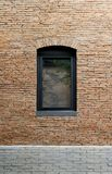 Black aluminum window frame in the building wall made of red brick royalty free stock images