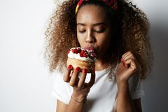 Black american african woman making a mess eating a huge fancy dessert over white background.  royalty free stock image