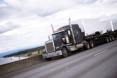 Black american big rig semi truck on interstate highway Royalty Free Stock Images