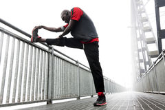 Black american runner stretch muscles. Before the race Royalty Free Stock Photo