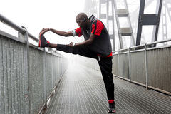 Black american runner stretch muscles before the race Royalty Free Stock Image