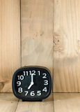 Black analog alarm clock on wood floor. At seven o'clock time in the morning, copy space royalty free stock image