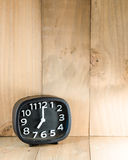 Black analog alarm clock on wood floor. At seven o'clock time in the morning, copy space stock photography