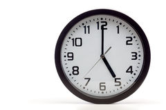 Black analog clock. Analog clock with black frame, showing 5 o'clock as typical end of office hours. Cutout, studio shot, isolated on white background stock photo