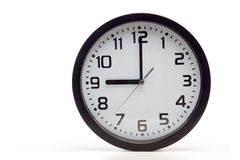 Black analog clock. Analog clock with black frame, showing 9 o'clock as typical start of working hours. Cutout, studio shot, isolated on white background stock photography