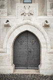 Black ancient metallic door in old stone wall Royalty Free Stock Photography