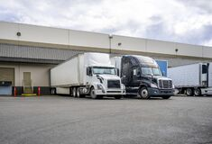Free Black And White Big Rigs Semi Trucks With Semi Trailers Loading Cargo At Warehouse Dock With Gates For Each Royalty Free Stock Images - 188130029