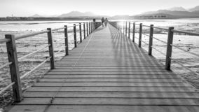 Free Black And White Image Of Long Wooden Pier In The Ocean. Calm Sea Waves And Amazing Sunset Over The Mountains Royalty Free Stock Photo - 148552765