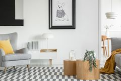 Free Black And White Poster Of Dog On The Wall Of Fashionable Living Room Interior With Two Wooden Coffee Tables With Flowers Stock Image - 156985941