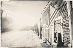 Free Black And White Sepia Vintage Photo Of Old Western Wooden Buildings With Flag Of The United States Stock Photography - 141699852