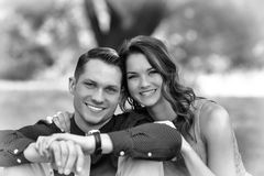 Black And White Version Of A Happy Young Couple Posing Seated On Royalty Free Stock Images