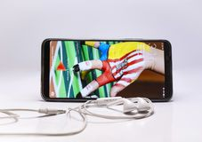Black Android Smartphone Beside White Earphones Royalty Free Stock Photo