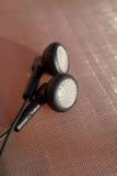 Black anonymous earphones on a metallic network Royalty Free Stock Image