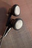 Black anonymous earphones on a metallic network Stock Images