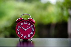 Black Antique Clock Red Metal Alarm Clock on Red Valentine`s Day stock photo
