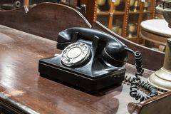 Black antique vintage analog telephone dialing. Black antique vintage analog telephone dialing or scrolling phone on wooden table. Contact us concept Royalty Free Stock Images