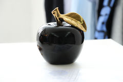 Black apple. Ceramic apple black mirror gold Royalty Free Stock Image