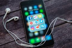 Black Apple iPhone with icons of social media and white headset stock photo