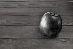 Black apple lies on a gray wooden table against stock photography