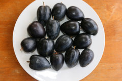 Black Apple on a plate Royalty Free Stock Image