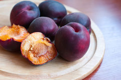 Black apricot. Group of black, or violet, apricots also called pluots lying on wooden plate on the table. Some fruit are cut in halves. Natural light Royalty Free Stock Photos
