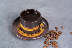 Black arabica coffee cup and coffee beans on grey background. Black arabica coffee cup and roasted coffee beans on grey background Royalty Free Stock Image